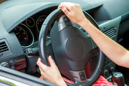 Car interior. Dashboard and woman hands on steering wheel driving a car.