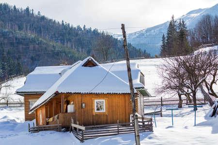 Hermosas y acogedoras casas de cabaña residenciales tradicionales ecológicas de madera de un piso con terraza, ático y techo empinado cubierto de nieve en la ladera de la montaña en un día soleado de invierno frío.