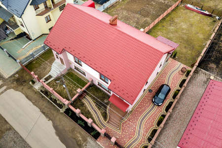 Aerial top view of house with shingle roof and brick chimney in quiet neighborhood, black car on paved yard. Well maintained property concept.