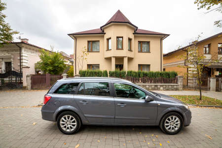 New expensive gray car parked in paved parking lot in front of big two story cottage. Luxury and prosperity concept. Stock fotó