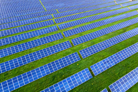 Large of solar voltaic panels system producing renewable clean energy on green grass .