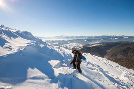 Tourist hiker climber in winter clothing with backpack climbing dangerous rocky steep mountain slope covered with deep snow, white sun rays shining in bright blue sky copy space background.