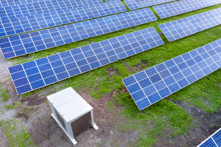 Large field of solar voltaic panels system producing renewable clean energy on green grass .