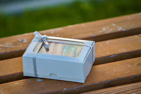 Cardboard white gift box with colorful handmade macaron cookies on wooden bench outdoors. 免版税图像