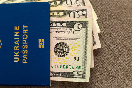 Ukrainian passport and money, American dollars banknotes bills on   , top view. Traveling and  finance problems concept.