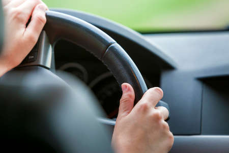Mani di donna sul volante alla guida di un'auto. Archivio Fotografico