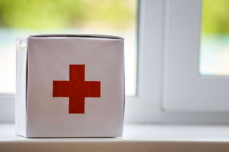 White first aid kit with red cross indoors on windowsill on blurred background. Healthcare concept. Фото со стока