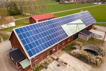 Top view of blue solar photo voltaic panels system on wooden building, barn or house roof. Renewable ecological green energy production concept. Zdjęcie Seryjne