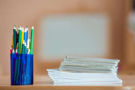 Wooden colorful drawing pencils arranged in plastic jug and stack of copybooks on light copy space background. Stock Photo