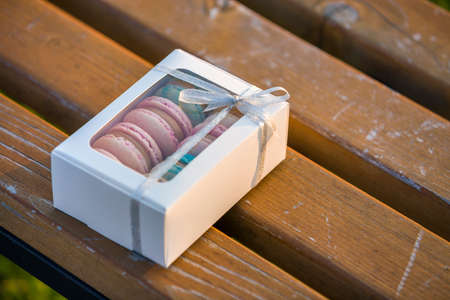 Cardboard white gift box with colorful handmade macaron cookies on wooden bench outdoors.