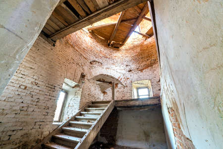 Large spacious forsaken empty basement room of ancient building or palace with cracked plastered brick walls, small windows, dirty floor and wooden staircase ladder.