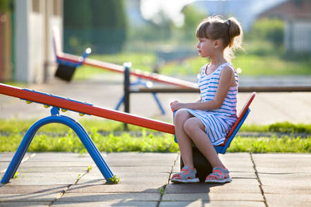 Cute young child girl outdoors on see-saw swing on sunny summer day.