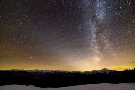 Winter mountains night landscape panorama. Milky Way bright constellation in dark starry sky, soft glow on horizon after sunset, magnificent mountain ridge snow-capped peaks, snowy steep woody hill. Stock Photo