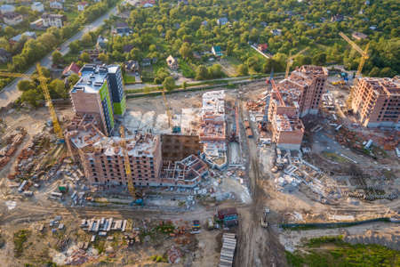Apartment or office brick buildings under construction, top view. Building site with tower cranes from above. Drone aerial photography. Stock Photo