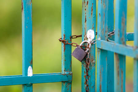 Old rusty fence or gate with chained padlock. Banco de Imagens