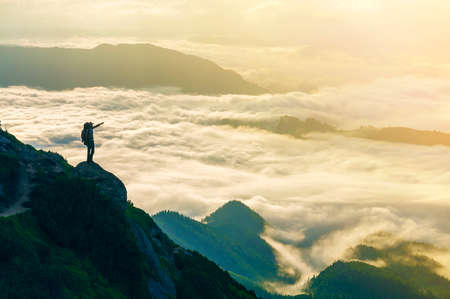 Wide mountain panorama. Small silhouette of tourist with backpack on rocky mountain slope with raised hands over valley covered with white puffy clouds. Beauty of nature, tourism and traveling concept 写真素材