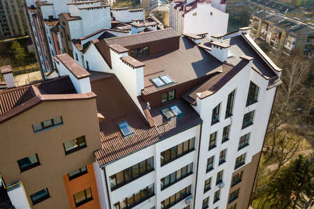 Aerial top view of new tall apartment building with annex room covered with metal siding and attic windows in quiet area. 版權商用圖片