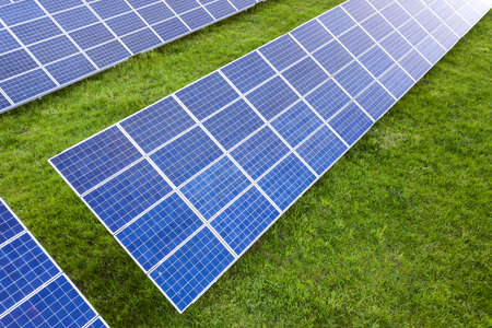 Surface of solar photo voltaic panels system producing renewable clean energy on green grass background. Stockfoto