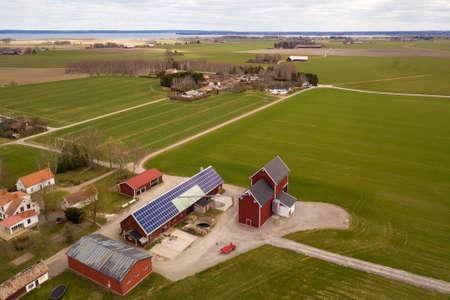 Widok z góry na wiejski krajobraz w słoneczny wiosenny dzień. Farma z systemem fotowoltaicznych paneli słonecznych na drewnianym budynku, stodole lub dachu domu. Pole zielone tło kopii przestrzeni. Produkcja energii odnawialnej.