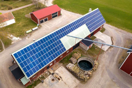 Top view of rural landscape on sunny spring day. Farm with solar photo voltaic panels system on wooden building, barn or house roof. Green field copy space background. Renewable energy production.
