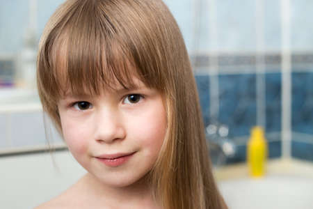 Pretty girl face portrait, smiling child with beautiful eyes and long wet fair hair on blurred background of bathroom.
