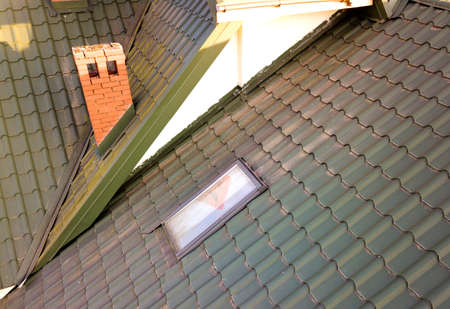 Close-up of new attic plastic window installed in shingled house roof. Professionally done building and construction work, roofing and installation concept. Stock Photo