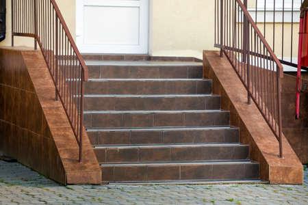 Scale in cemento ricoperte di piastrelle di ceramica con ringhiere metalliche all'aperto. Archivio Fotografico