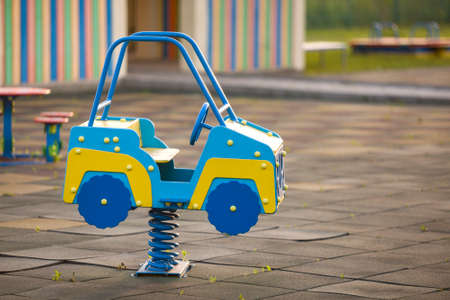 Kindergarten playground with bright toy car on spring. Children activities and recreation outdoors. Banco de Imagens