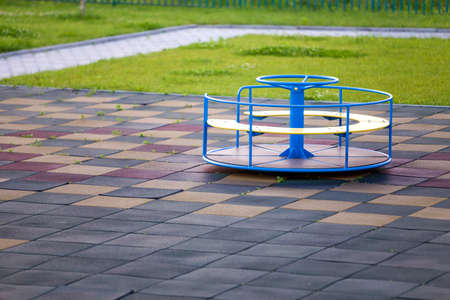 Playground in kindergarten with soft flooring and colorful bright merry-go-round outdoors.