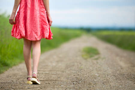 Back view of young woman in red dress legs walking by ground road on summer day on blurred sunny background. Banco de Imagens