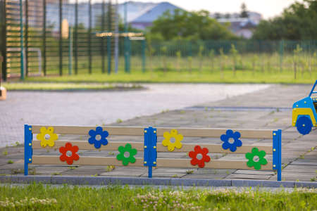 Multicolored wooden or plastic low decorative fence outdoors on sunny summer day. Banco de Imagens