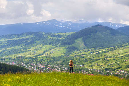 Back view of slim young woman standing on grassy valley on background of green mountains on sunny summer day.