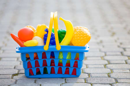 Bright plastic colorful basket with toy fruits and vegetables outdoors on sunny summer day.