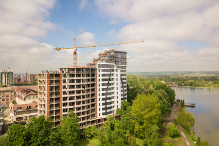 Apartment or office tall building unfinished under construction among green tree tops. Tower cranes on bright blue sky copy space background. Banco de Imagens