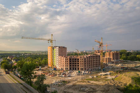 Aerial view of building site. Apartment or office building under construction. Tower cranes on suburb landscape and blue sky copy space background.