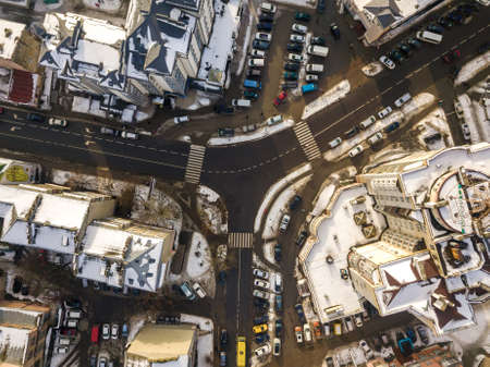 Aerial black and white winter top view of modern city with tall buildings, parked and moving cars along streets with road marking. Urban cityscape, view from above.