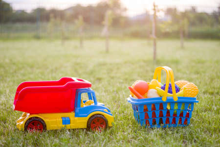 Car truckand a basket with toy fruit and vegetables. Bright plastic colorful toys for children outdoors on sunny summer day. Banco de Imagens