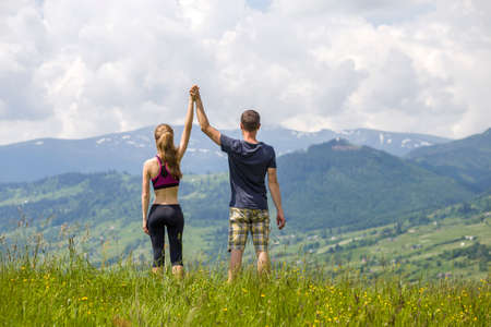 Young couple, sportive man and slim woman holding hands outdoors on background of beautiful mountain landscape on sunny summer day, back view.