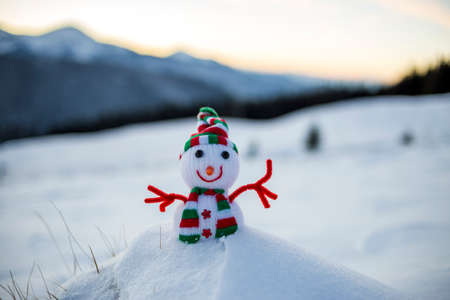 Small funny toy baby snowman in knitted hat and scarf in deep snow outdoor on blurred snow covered mountains landscape background. Happy New Year and Merry Christmas greeting card theme.