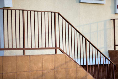 Concrete stairs covered with ceramic tiles with metal railings outdoors. Stock Photo