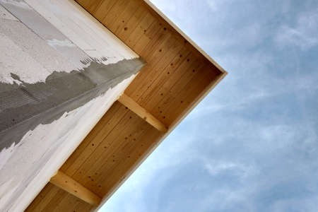 Low angle view of a building fasade under construction unfinished wall and wooden roof boards.