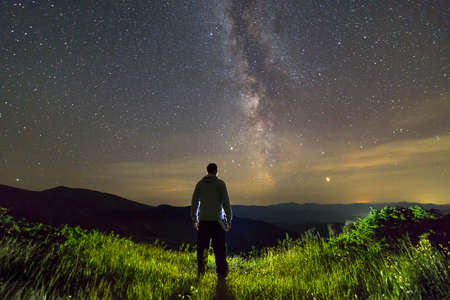 Dark silhouette of a man standing in mountains at night enjoying milky way view.