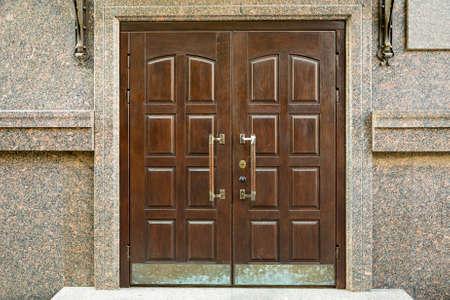 New big wooden oak doors with brass handles. Imagens