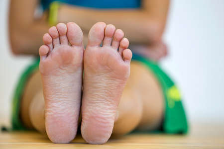 Close-up of woman sitting on the floor with bare feet. Legs care and skin treatment concept.