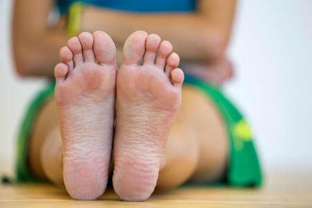 Close-up van vrouw zittend op de vloer met voeten. Benen zorg en huid behandeling concept.