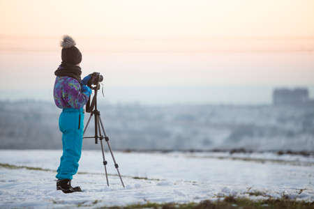 Child boy taking pictures outside in winter with photo camera on a tripod on snow covered field. 스톡 콘텐츠