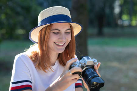 Pretty teenage girl with red hair taking picture with photo camera in summer park. 스톡 콘텐츠