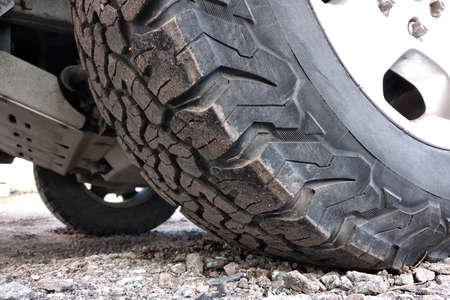 All terrain car tire on a wheel.