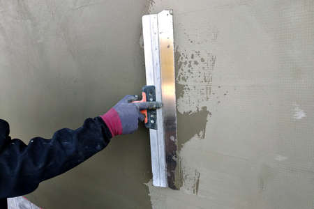 Worker covering insulated wall with solution of glue over plastered foam insulation.