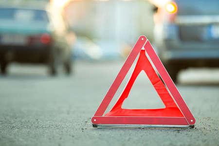 Rotes Notfall-Dreieck-Stopp-Schild und kaputtes Auto auf einer Stadtstraße.